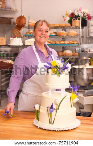 A woman pastry chef completes the decoration of a wedding cake in a bakery setting with a bench in the foreground and bakery products in the background. - stock photo