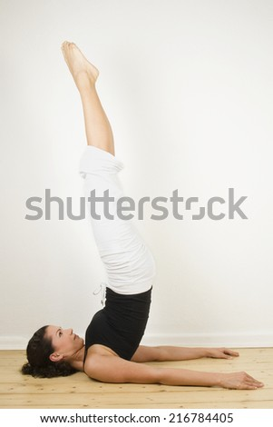 A woman performing the shoulder stand.