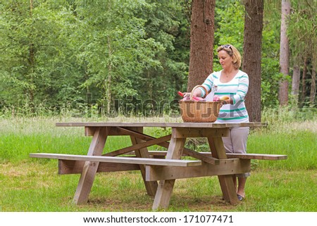 A woman placing a whicker picnic basket full of food and drink on a table in woodland, on a bright summers day. - stock photo