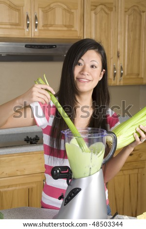 A woman placing celery into her healthy smoothie with a smile on her face. - stock photo