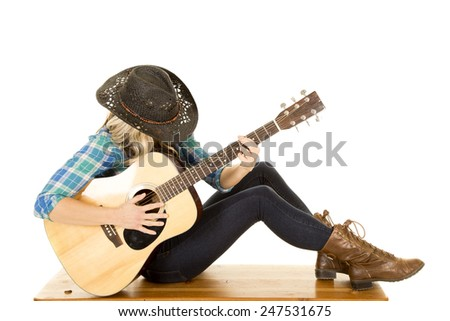 a woman playing her guitar with her head down, sitting on a bench. - stock photo