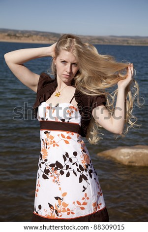 a woman playing with her hair with a serious expression on her face. - stock photo