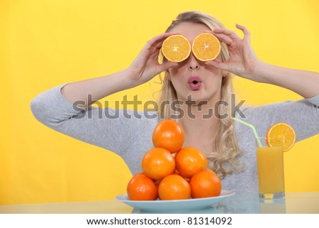 A woman playing with oranges