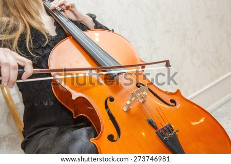 a woman plays the brown violin on a light background