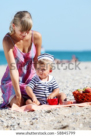 A woman plays with a child on the sea in summer