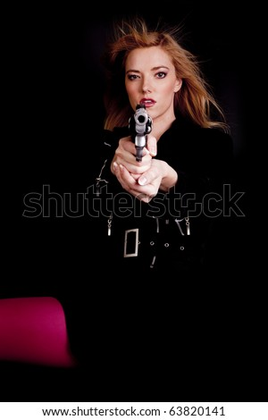 A woman pointing her gun at the camera with a serious expression on her face. - stock photo