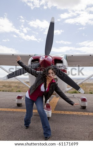 A woman posing in front of an airplane. - stock photo
