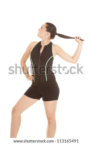 A woman posing in her work out clothes holding on to her pony tail - stock photo