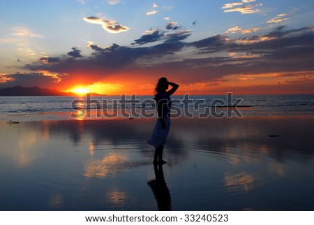 A woman posing in the water during a sunset - stock photo