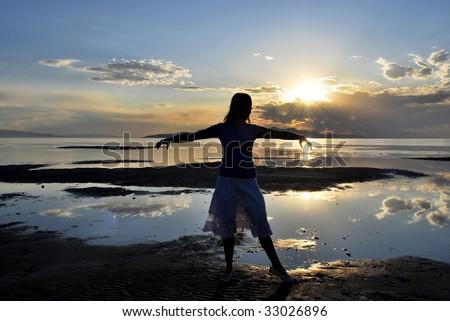 A woman posing near a lake at sunset - stock photo