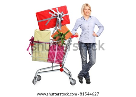 A woman posing next to a shopping cart full with gifts isolated on white background - stock photo