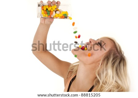 A woman pouring a glassful of colorful jelly beans into her mouth. - stock photo