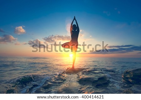 A woman practices yoga on a background of sea and sky with clouds - stock photo