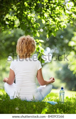 A woman practices yoga outdoors
