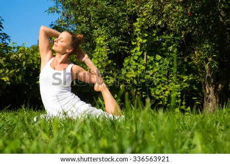 A woman practicing Yoga in the park on a sunny day.
