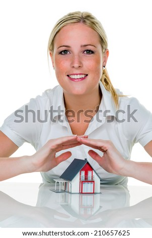 a woman protects with hands a haus.symbolfoto for insurance and building savings.