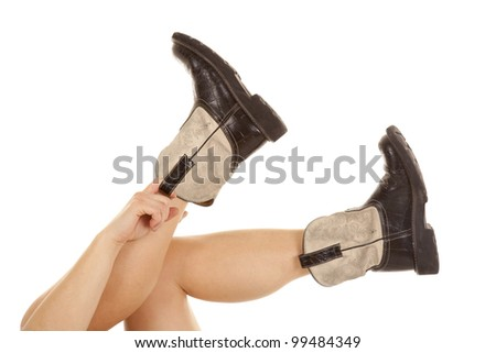 A woman pulling on her cowboy boots on to her feet. - stock photo