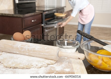 A woman pulls out a freshly baked pic from an oven while other ingredients await to be made into another pie.