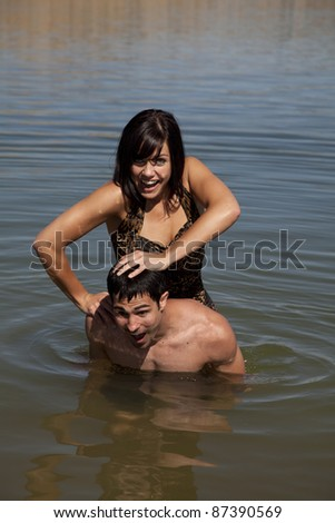 A woman pushing her man's head in the water laughing. - stock photo