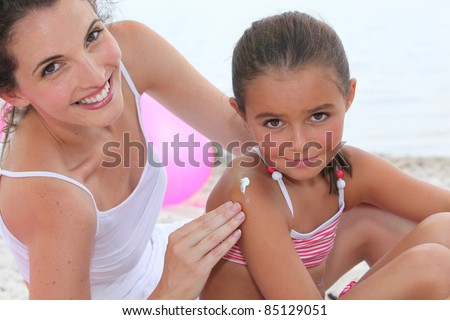A woman putting suncream on her daughter. - stock photo