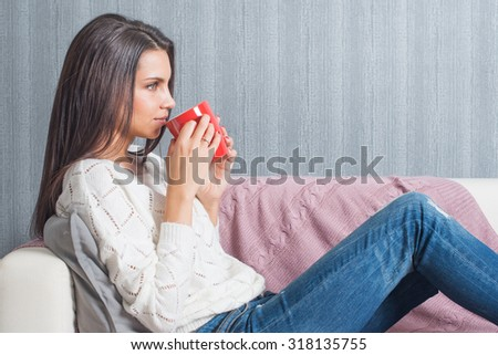 A woman  raising a red mug with coffee, tea to his lips smiles lying on the couch, sofa.