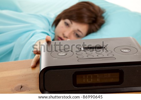 A woman reaching out for her alarm clock trying to get a few more minutes of sleep in. - stock photo