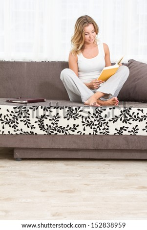 A woman reading a book and smiling as she sits on sofa in room - stock photo