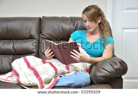A woman reading a book on a couch - stock photo