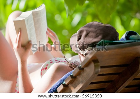 A woman reading a book on her sunlounger - stock photo