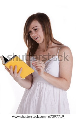 A woman reading an laughing at her yellow book.
