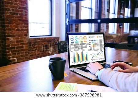 A woman reading graphic charts on laptop. - stock photo