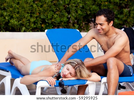 A woman receiving a back massage on a pool chair - stock photo