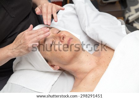 A woman receiving a facial or skin treatment at a clinic. - stock photo