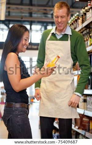 A woman receiving help from a grocery store clerk - critical focus on woman - stock photo