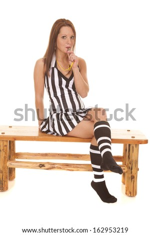 A woman referee is holding her whistle to her lips. - stock photo