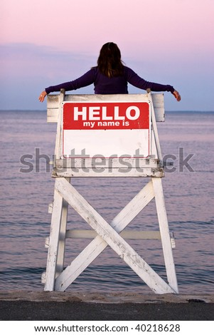 A woman relaxes in a vacant lifeguard chair where the sign on the back reads HELLO MY NAME IS. - stock photo