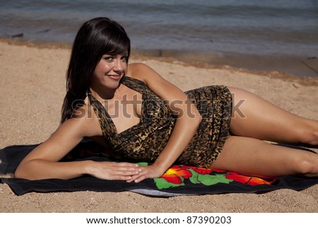 a woman relaxing and getting some sun while she is laying out on the beach. - stock photo
