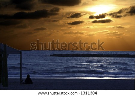 A woman relaxing and meditating at sundown on the Mediterranean beach called ?banana beach?, - stock photo