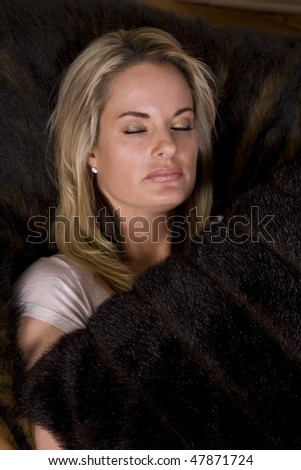 A woman relaxing and sleeping on her couch while holding her pillow. - stock photo