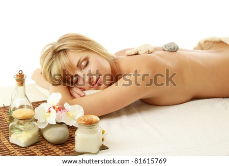 A woman relaxing during a stone therapy on white background - stock photo