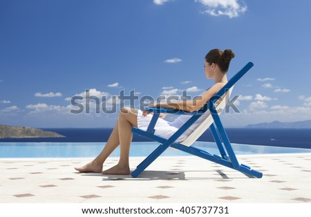 A woman relaxing in a deck chair - stock photo