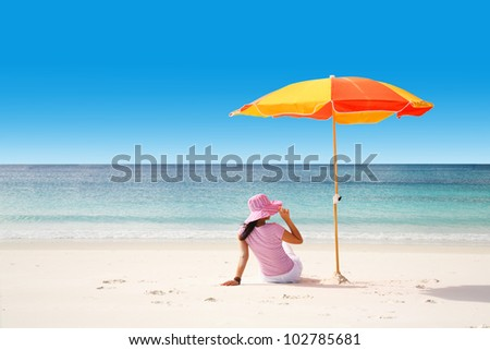 A woman relaxing in a tropical beach. Copy space available for your text - stock photo