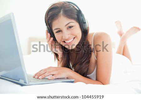 A woman relaxing on a bed, using a laptop and headphones with her legs crossed, she is also smiling. - stock photo