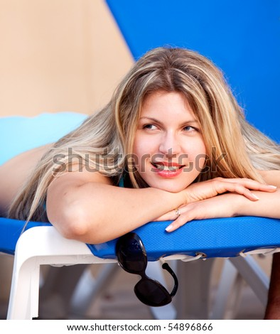 A woman relaxing on a pool side beach chair - stock photo