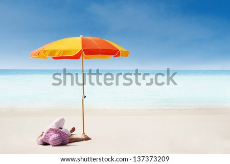 A woman relaxing on the beach in Whitsunday island; Australia - stock photo