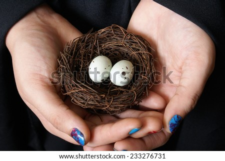 A woman rescues a couple eggs from the wild to give the unhatched birds a second chance. - stock photo