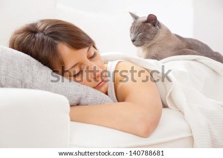 A woman resting in bedroom/ Portrait of a young woman sleeping on the bed - stock photo
