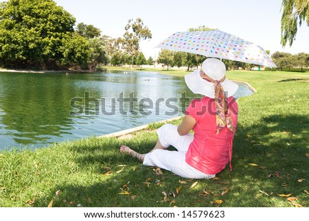 A woman rests at a park lake while using a colorful umbrella to protect herself from the sun.