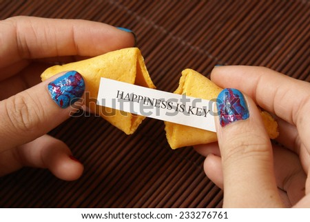 A woman reveals her hidden message within the fortune cookie. - stock photo