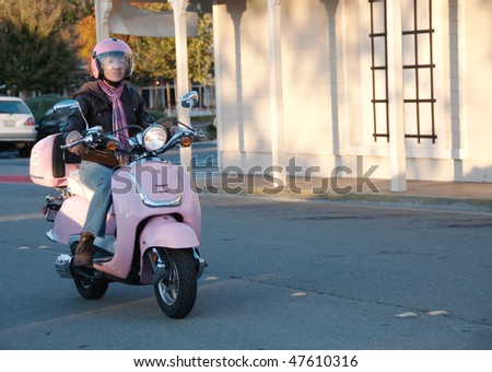 a woman rides her pink scooter with copy space on the right - stock photo